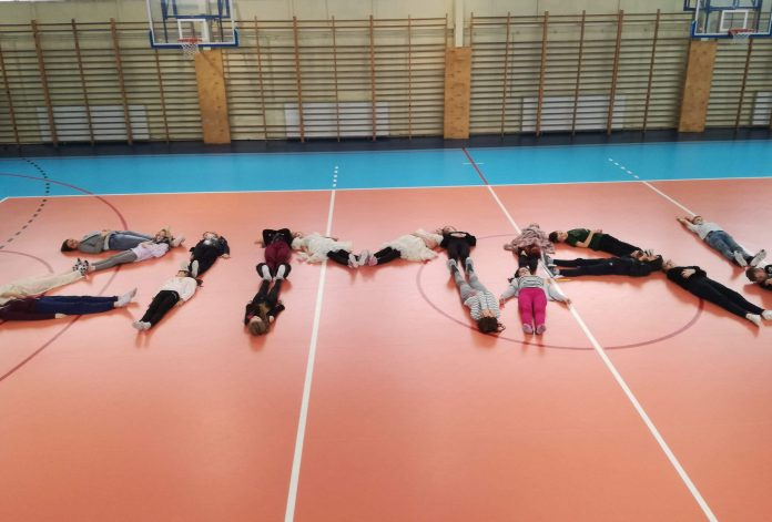 Zdjęcie pokazuje dzieci na sali gimnastycznej, które leżąc na podłodze układają napis ZIMA