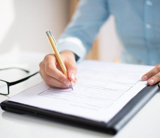 Wypełnij wniosek, kobieta wypełnia dokument - foto: Katemangostar / Freepik.com