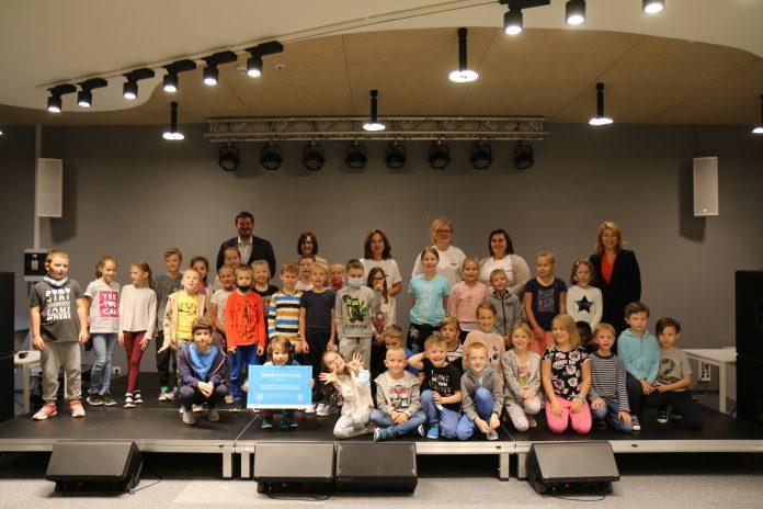 Zdjęcie grupowe uczestników spotkania: przedstawiciele firmy Microsoft, Nauczyciele, dyrekcja szkoły, zastępca burmistrza oraz dzieci