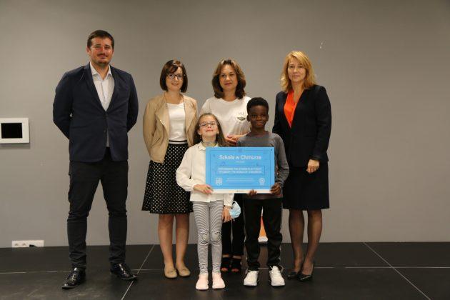 Na zdjęciu przedstawiciele urzędu, szkoły oraz dzieci trzymające tabliczkę z napisem Szkoła w Chmurze Microsoft