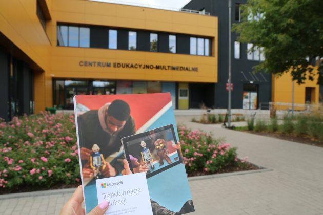 Zdjęcie przedstawia książkę Microsoft na tle budynku Centrum Edukacyjno-Multimedialnego w Piasecznie