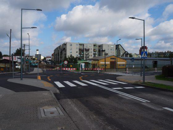 skrzyżowanie ulic Nadarzyńskiej i Dworcowej w Piasecznie, pachołki uniemożliwiają wjazd na część ulicy Dworcowej, gdzie nadal trwają prace. W oddali widać kościół i blok mieszkalny.