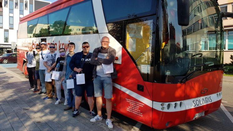 Grupa krwiodawców stojąca przed biało-czerwonym autobusem PCK