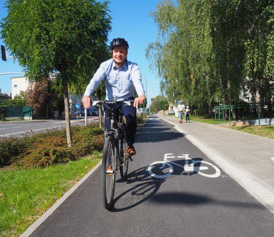 Na zdjęciu Daniel Putkiewicz Burmistrz Miasta i Gminy Piaseczno jadący rowerem po ścieżce rowerowej przy ul. Powstańców Warszawy w Piasecznie, na głowie ma kask.