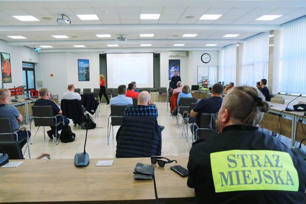 Szkolenia Strażników Miejskich. Na zdjęciu osoby biorące udział w szkoleniu na sali konferencyjnej, które słuchają wykładu instruktora. Na pierwszym planie napis Straż Miejska na koszulce strażnika.