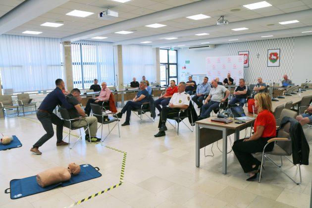 Szkolenia Strażników Miejskich. Na zdjęciu osoby biorące udział w szkoleniu na sali konferencyjnej, które oglądają praktyczny pokaz wyciągania rannej osoby z samochodu.