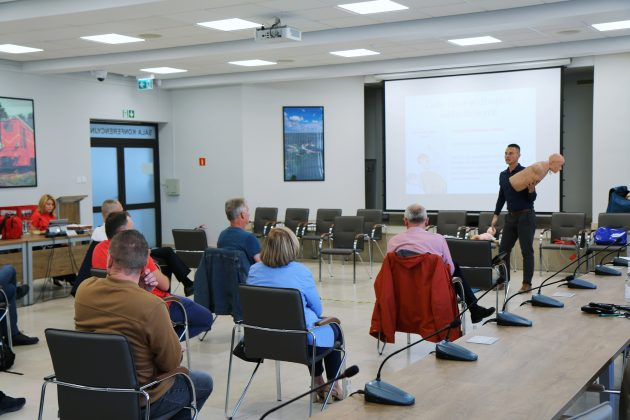 Szkolenia Strażników Miejskich. Na zdjęciu osoby biorące udział w szkoleniu na sali konferencyjnej oraz instruktor, który trzyma w ręku fantoma medycznego.
