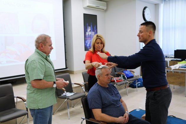 Szkolenia Strażników Miejskich. Na zdjęciu wiceburmistrz oraz dwóch strażników uczy się poprawnego bandażowania, podczas urazów głowy. Instruktor objaśnia temat.