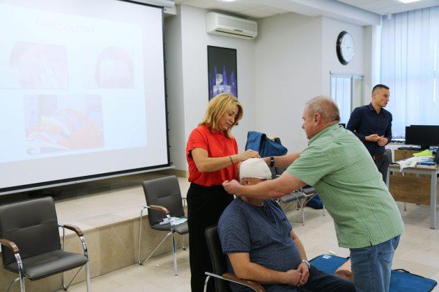 Szkolenia Strażników Miejskich. Na zdjęciu wiceburmistrz oraz dwóch strażników uczy się poprawnego bandażowania, podczas urazów głowy. Instruktor w tle objaśnia temat pozostałym osobom biorącym udział w szkoleniu.