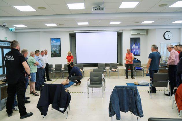 Szkolenia Strażników Miejskich. Na zdjęciu strażnicy podzieleni na grupy, ćwiczą na fantomach medycznych resuscytacji krążeniowo-oddechowej.