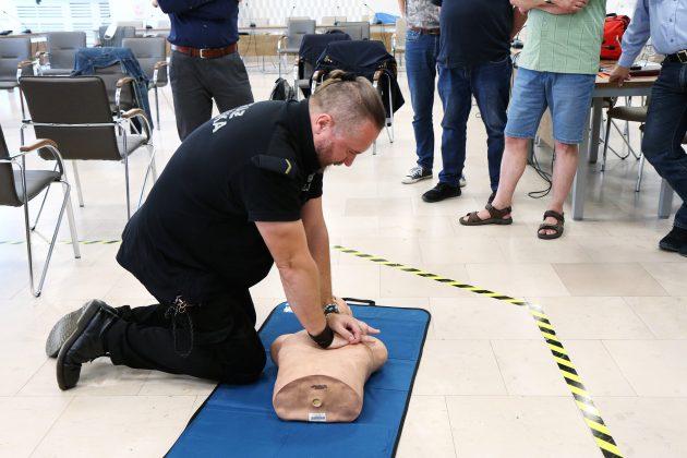 Szkolenia Strażników Miejskich. Na zdjęciu jeden ze strażników ćwiczy na fantomie medycznym resuscytację krążeniowo-oddechową, pozostali strażnicy stoją dookoła ćwiczącej osoby.