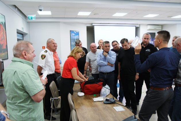 Szkolenia Strażników Miejskich. Na zdjęciu instruktor omawia zawartość torby pierwszej pomocy, która jest na wyposażeniu Straży Miejskiej w Piasecznie. Strażnicy przysłuchują się uważnie wykładowi.