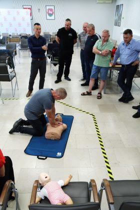Szkolenia Strażników Miejskich. Na zdjęciu strażnicy ćwiczą na fantomie medycznym resuscytacji krążeniowo-oddechowej. Instruktor objaśnia sposób uciskania, natomiast jeden ze strażników miejskich uciska fantoma. Pozostali strażnicy oglądają ćwiczenie stojąc z boku.