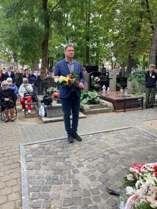 elegancko ubrany mężczyzna z kwiatami składa hołd pod pomnikiem Katyńskim