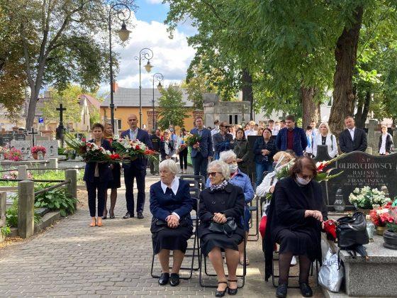 widok na uczestników uroczystości. Część osób stoi pod drzewami, część zajęła miejsca siedzące.