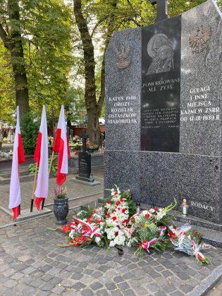 """Pomnik Katyński z szarego kamienia, u jego szczytu napis """"pomordowani ale żyją..."""". pod pomnikiem złożone wieńce, a obok trzy biało czerwone flagi."""
