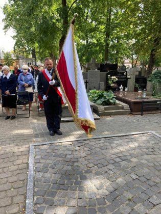 mężczyzna przepasany biało-czerwona wstęgą staje pod pomnikiem katyńskim ze sztandarem, w tle uczestnicy uroczystości i cmentarz
