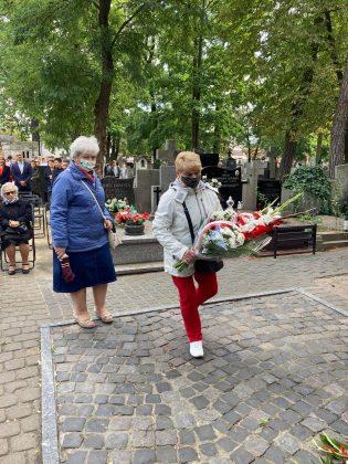 dwie starsze kobiety idą z kwiatami w stronę pomnika. Ich twarze zakrywają maseczki ochronne.