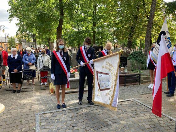 Młodzież szkolna - chłopiec i dwie dziewczynki w odświętnych strojach oddają hołd pod pomnikiem