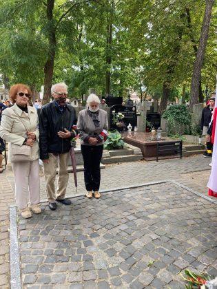 trójka starszych osób, dwie kobiety i mężczyzna stoją pod pomnikiem. Ich twarze zakrywają maseczki ochronne.