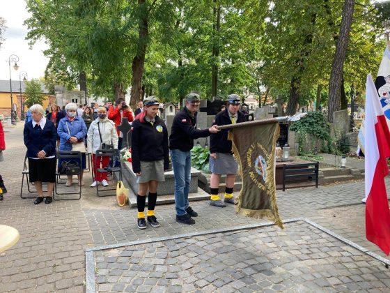 troje harcerzy ze sztandarem stoi pod pomnikiem katyńskim, ubrani w stroje harcerskie. W tle starsze kobiety obecne na uroczystości.