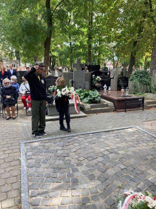 Mała dziewczynka z bukietem białych kwiatów i starszy od niej harcerz w mundurze oddają hołd pod pomnikiem.