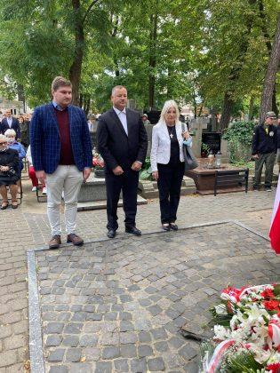 trzy osobowa delegacja - jedna kobieta i dwóch mężczyzn - stoją pod Pomnikiem Katyńskim, za ich plecami uczestnicy uroczystości.