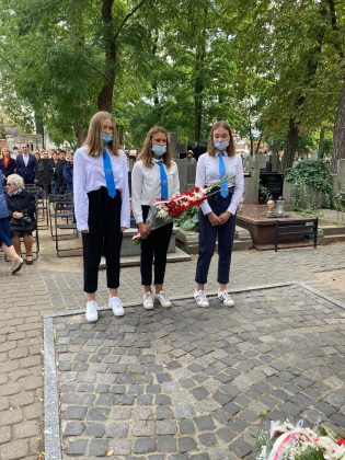 Młodzież szkolna - trzy młode dziewczyny w odświętnych strojach oddają hołd pod pomnikiem.Młodzi ludzie maja na sobie białe koszule i niebieskie krawaty.