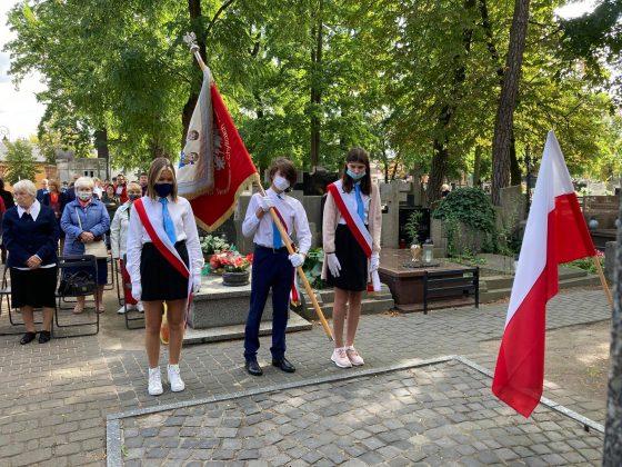 Młodzież szkolna - chłopiec i dwie dziewczynki w odświętnych strojach oddają hołd pod pomnikiem. Młodzi ludzie maja na sobie białe koszule i niebieskie krawaty.