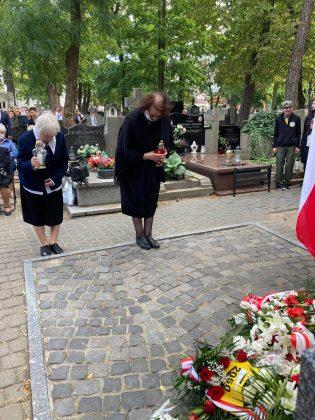 Dwie starsze kobiety w ciemnych strojach składaja kwiaty pod pomnikiem katyńskim