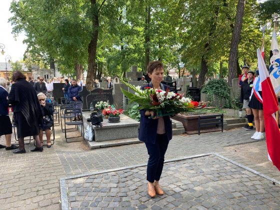 Członek Zarządu Powiatu Piaseczyńskiego Ewa Lubianiec składa pod pomnikiem wiązankę kwiatów w biało-czerwonych barwach. W tle uczestnicy uroczystości.