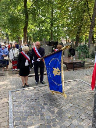 dwójka elegancko ubranych starszych ludzi - kobieta i męzczyzna , stoja pod pomnikiem ze sztandarem.