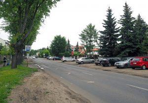 Rozbudowa drogi wojewódzkiej nr 722 ul. Księcia Janusza I Starego w Piasecznie. Na zdjęciu ulica, która będzie remontowana. Na poboczu stoją samochody.