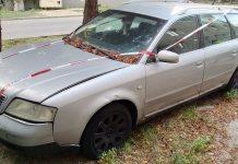 Ilustracja. Wraki pojazdów na terenie gminy Piaseczno. Na zdjęciu wrak srebrnego, opuszczonego samochodu oklejony taśmą straży miejskiej.