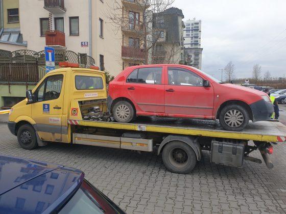 Ilustracja. Wraki pojazdów na terenie gminy Piaseczno. Na zdjęciu samochód laweta z odholowanym czerwonym samochodem. W tle bloki.