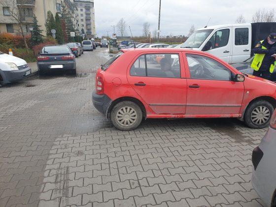 Ilustracja. Wraki pojazdów na terenie gminy Piaseczno. Na zdjęciu czerwony samochód odholowywany przez Straż Miejską w Piasecznie. W tle budynki i inne zaparkowane samochody.