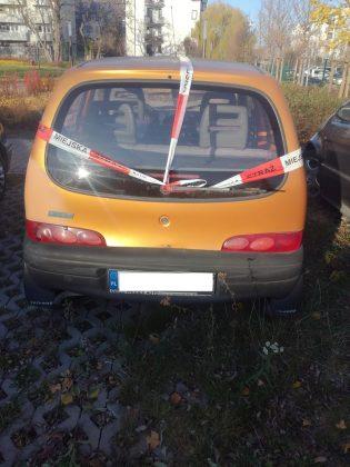 Ilustracja. Wraki pojazdów na terenie gminy Piaseczno. Na zdjęciu pomarańczowy samochód oklejony taśmą straży miejskiej.