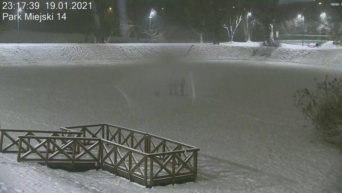 Zdjęcie. Zdjęcie przedstawia trzy osoby, które w dniu 19 stycznia 2021 w nocy na środku zamarzniętego stawu w Parku Miejskim w Piasecznie spożywały alkohol.