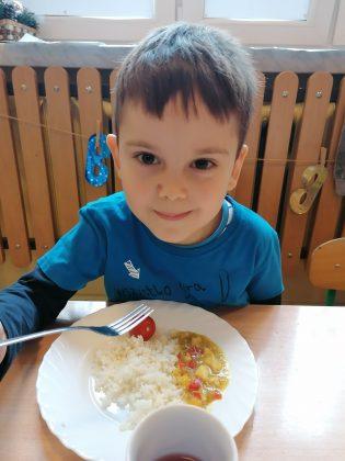 """Ilustracja. Kulinarna podróż do Indii w """"Nefrytowym Zakątku"""". Zdjęcie przedstawia chłopca ubranego w niebieską bluzkę jedzącego obiad- ryż basmati z warzywami w sosie ze złocisto-żółtego curry."""