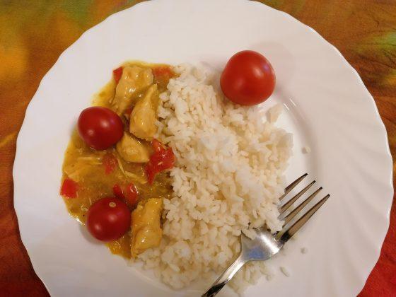 """Ilustracja. Kulinarna podróż do Indii w """"Nefrytowym Zakątku"""". Na zdjęciu talerz z typowym jedzeniem indyjskim- ryż basmati z warzywami w sosie ze złocisto-żółtego curry."""