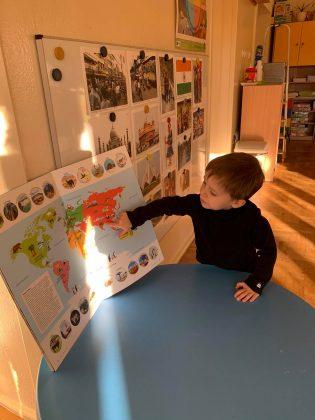 """Ilustracja. Kulinarna podróż do Indii w """"Nefrytowym Zakątku"""". na zdjęciu chłopiec ubrany w czarną bluzkę, opierający się o niebieski stół, pokazuje na mapie Indie. W tle na tablicy wiszą zdjęcia przedstawiające Indie."""