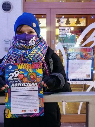 Ilustracja. Nefrytowy Zakątek wspiera WOŚP. Na zdjęciu kobieta trzymająca rozliczenie puszki WOŚP. W tle drzwi budynku.