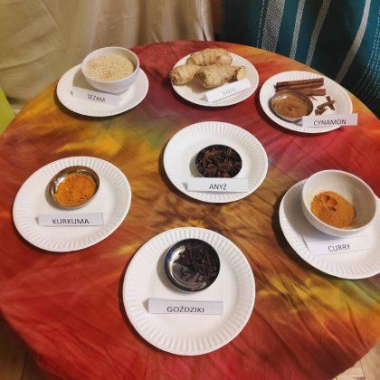 """Ilustracja. Kulinarna podróż do Indii w """"Nefrytowym Zakątku"""". Na zdjęciu znajduje sie stół, na którym jest rozstawionych 7 talerzy z przyprawami: kurkuma, goździki, curry, anyz, cynamon, sezam i imbir."""