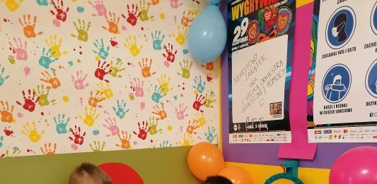 Ilustracja. Nefrytowy Zakątek wspiera WOŚP. Na zdjęciu chłopiec wrzucający pieniądze do puszki WOŚP, obok stoi chłopiec i dziewczynka.