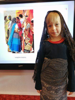 """Ilustracja. Kulinarna podróż do Indii w """"Nefrytowym Zakątku"""". na zdjęciu dziewczynka przebrana w typowy strój indyjski. W tle na ekranie zdjęcie kobiet ubranych w stroje indyjskie."""