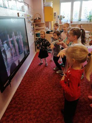 """Ilustracja. Kulinarna podróż do Indii w """"Nefrytowym Zakątku"""". Na zdjęciu grupa dzieci tańczy naśladując taniec indyjski, który oglądają w telewizji."""
