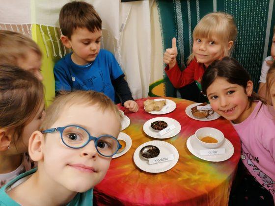"""Ilustracja. Kulinarna podróż do Indii w """"Nefrytowym Zakątku"""". Na zdjęciu grupa 6 dzieci siedząca przy stole. Na stole są rozstawione talerze a na nich przyprawy indyjskie."""