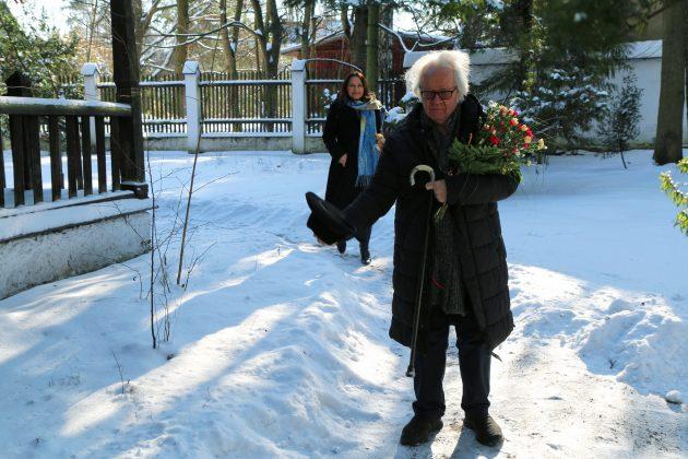 91. urodziny Józefa Wilkonia. Na zdjęciu Józef Wilkoń wita gości i trzyma w ręku laskę, kwiaty oraz kapelusz.