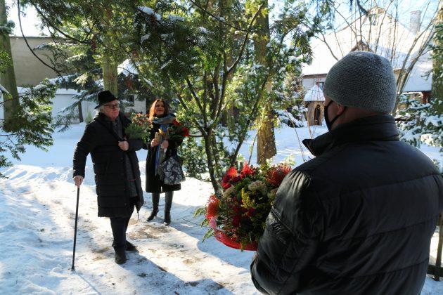 91. urodziny Józefa Wilkonia. 91. urodziny Józefa Wilkonia. Na zdjęciu Burmistrz Piaseczna Daniel Putkiewicz trzyma urodzinowe kwiaty, w tle stoi Józef Wilkoń z kwiatami i podpiera się laską.