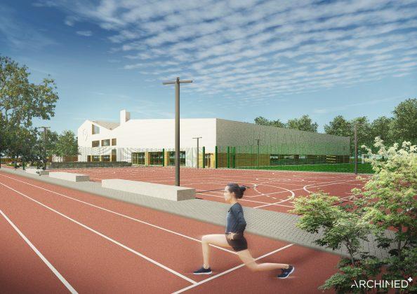 Ilustracja. Nowa szkoła i biblioteka w Julianowie- szkic. Zdjęcie przedstawia kompleks sportowy zlokolizowany na terenie szkoły. na zdjęciu widoczne boisko oraz bieżna, po której biegnie osoba. W oddali widać budynek szkoły oraz zieleń miejską.
